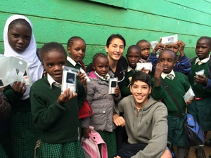 Dr. Marco and one of his sons with the Kibera school children and their new Luminaid lamps