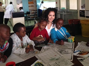 Emina, Dr. Marco's wife, coloring with the children in the hospital
